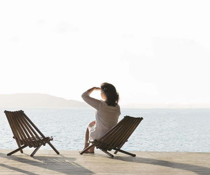 Woman on deck chair stares out to horizon