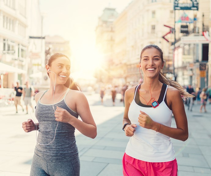 Two women jog through city