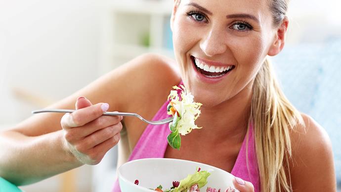 blonde woman eating salad