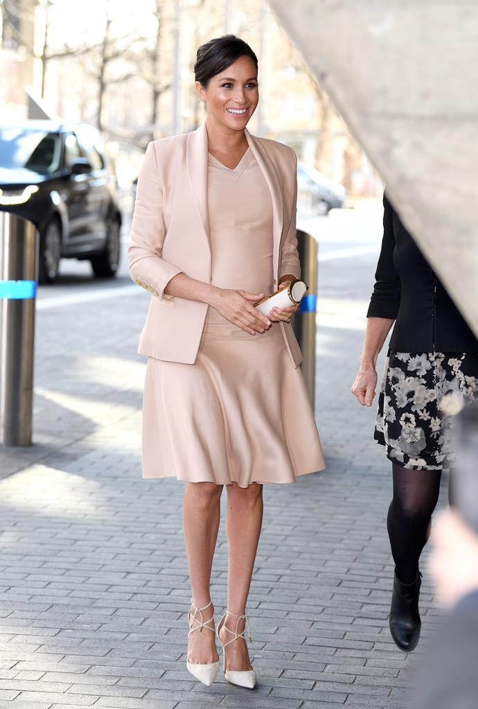 Duchess Meghan looked glowing in her beige outfit during her visit to the National Theatre. *(Source: Getty)*