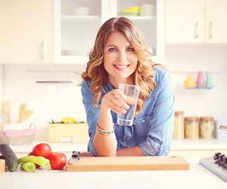 Woman smiling holding water in kitchen