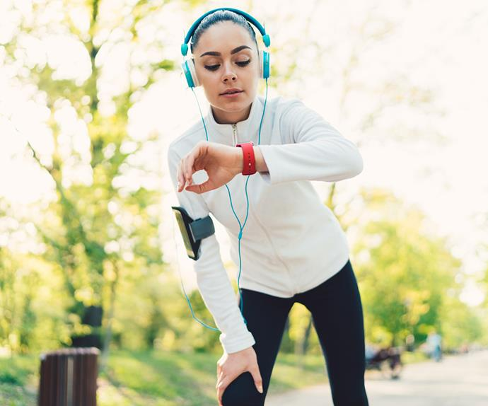 woman running looking at fitness tracker