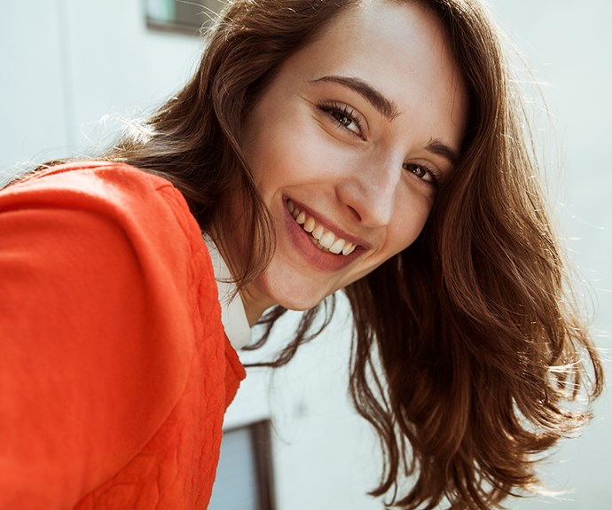 brunette girl smiling in red top