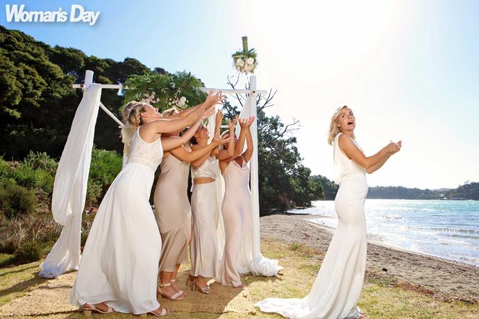 "In a toss to tradition, the bride throws her bouquet. ""Catch my good luck, girls!"""
