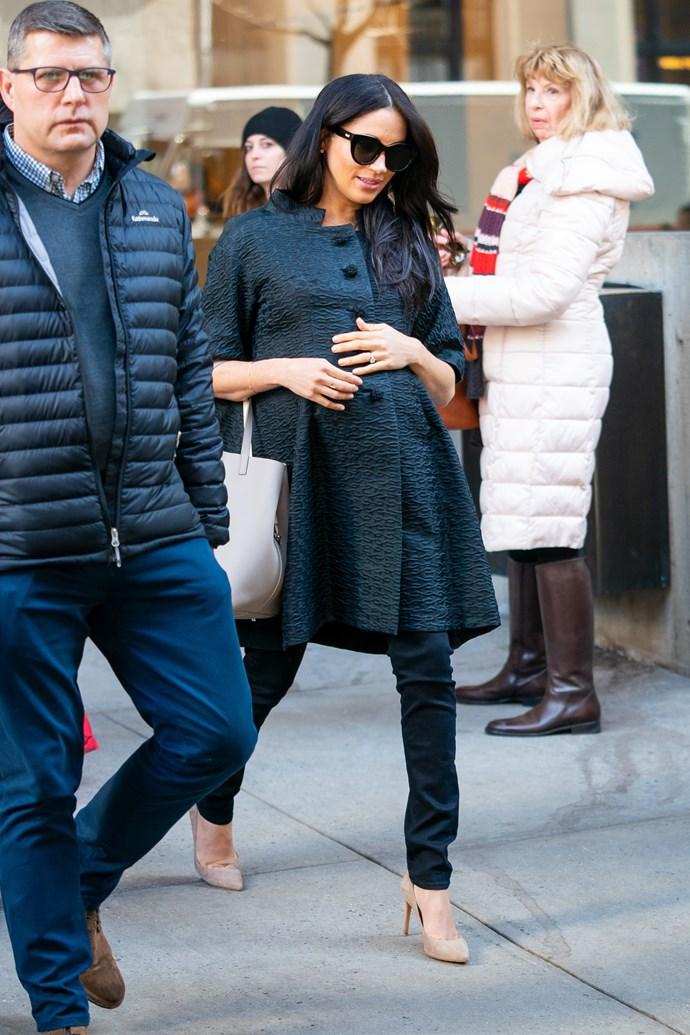 Meghan looked effortlessly chic in a dark grey coat, black skinny jeans, beige heels and dark sunglasses. *(Image: Getty)*