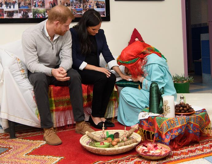 Prince Harry watches as Duchess Meghan receives a henna tattoo to celebrate and mark her pregnancy. *(Image: Getty)*