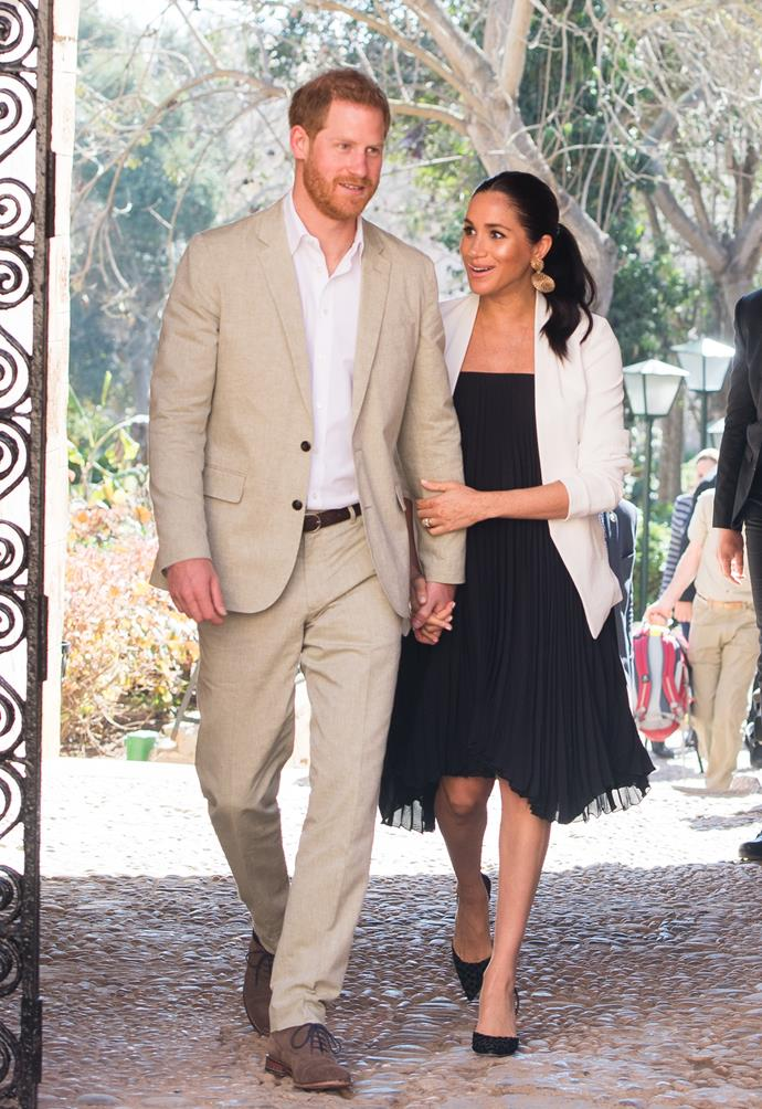 Harry looked smart in a tan coloured suit, while Meghan wowed in a classic LBD. *(Image: Getty)*