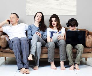 Family of four sit on couch all using electronic devices