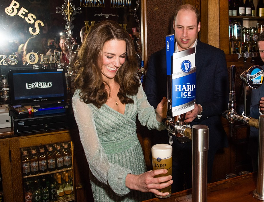 The Duke and Duchess get the party started by both pulling a pint of beer. *(Image: Getty)*