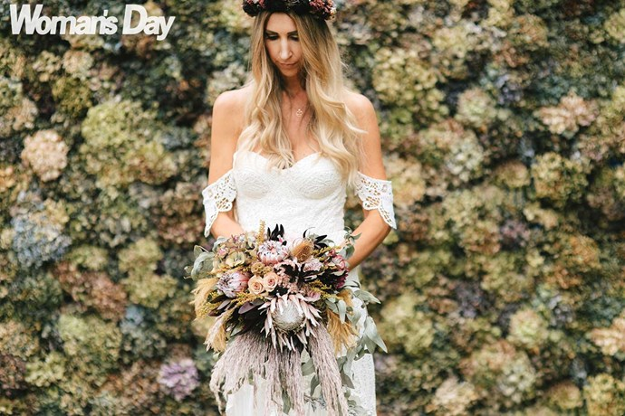 Kristie stands in front of the wall that was made with 1800 dried hydrangea blooms.