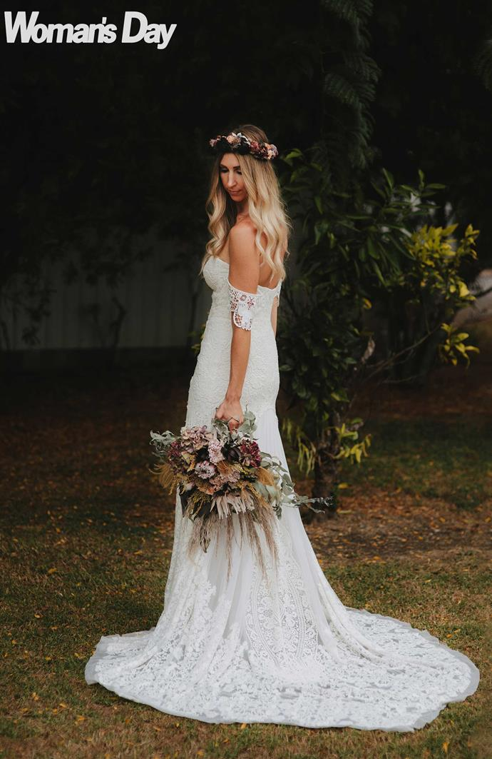 The beautiful bride is a bohemian dream in her embroidered lace gown.