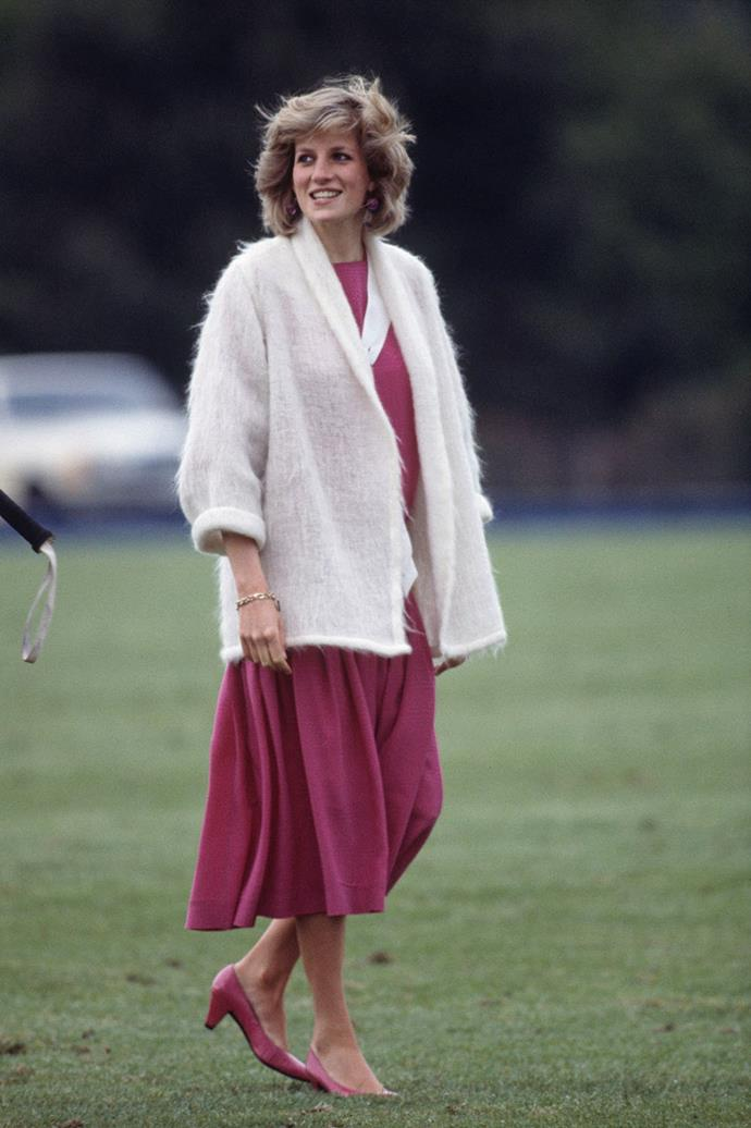 **Princess Diana, 1984**  While pregnant with her second son, Prince Harry, Princess Diana opted for a pink shift dress paired with matching ballet flats and a fluffy white cardigan while attending a polo match. *(Image: Getty)*