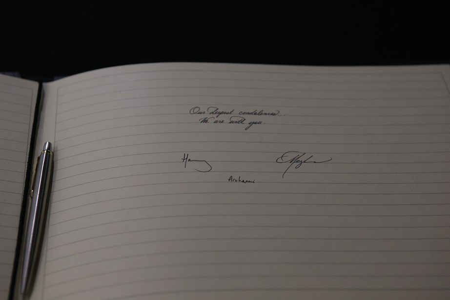 Meghan's impeccable handwriting can be seen in the book of condolence at New Zealand House. *(Image: Getty)*
