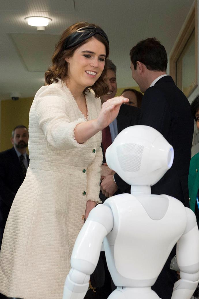 Just days before her birthday, Princess Eugenie visited the Royal National Orthopaedic Hospital with her father Prince Andrew and husband Jack Brooksbank to open their new Stanmore Building. This snap of the princess meeting a robot called Pepper is one of our favourites from the day. *(Image: Getty)*