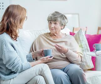 Elderly mother and adult daughter talk on couch