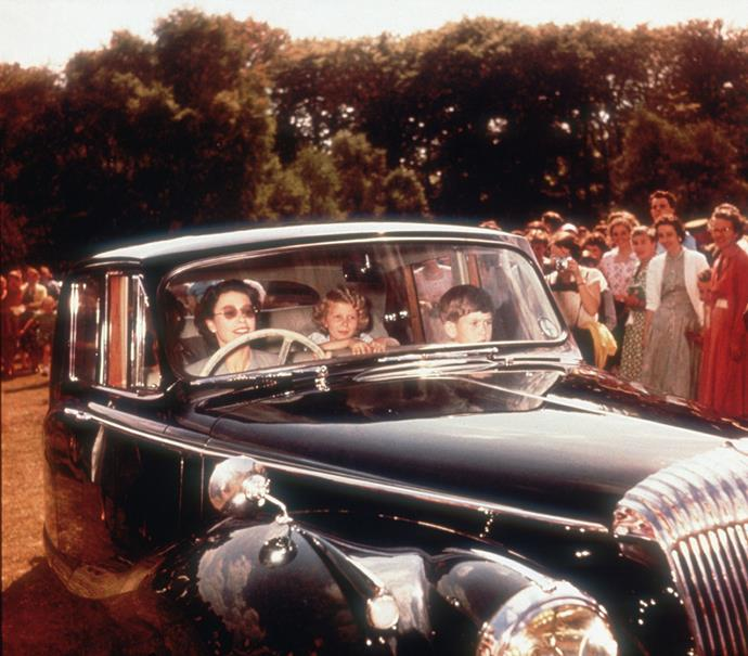Queen Elizabeth driving Princess Anne and Prince Charles at Windsor in 1957. *(Image: Getty)*