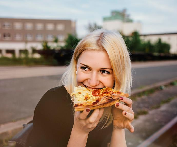 blonde woman happily eating pizza