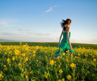 woman walking in a field of yellow flowers