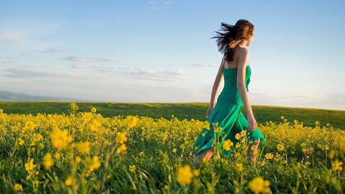 woman walking in a field of yellow flowers