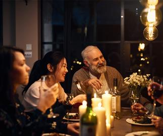 people of all ages round a table at dinner party