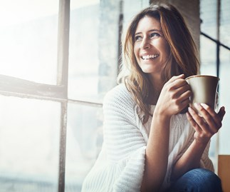 woman smiling and looking out window while drinking tea