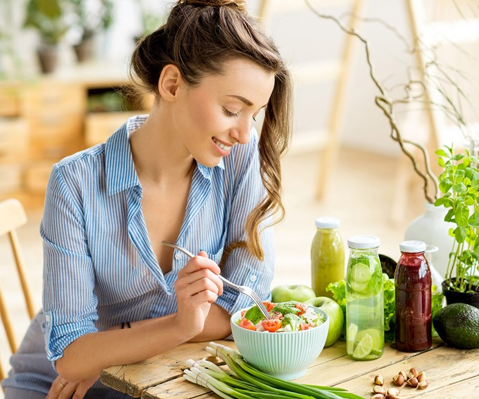 woman eating a salad surrounded by green vegetables on her table