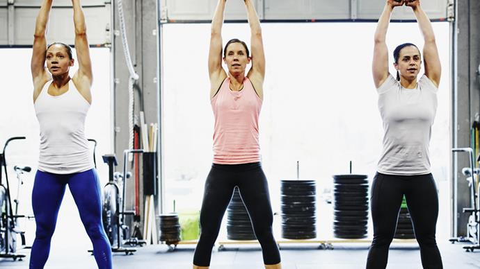 Line of women lifting weights above their heads high intensity workout