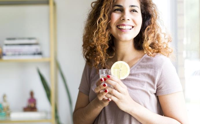 happy woman stands near window holding lemon water