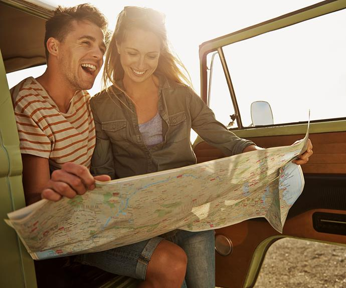 Couple sitting in truck consult map happily