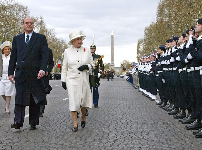 The Queen walking down Champs-Elysees in Paris in 2004. *(Image: Getty)*