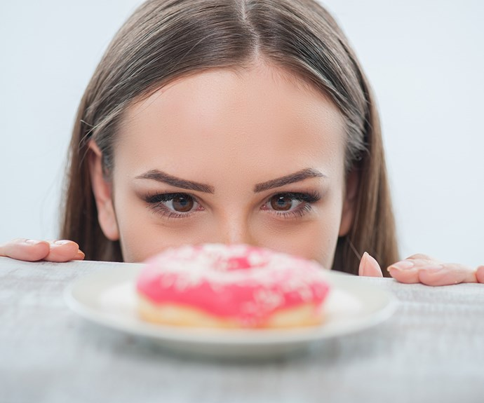 woman staring at a pink donut