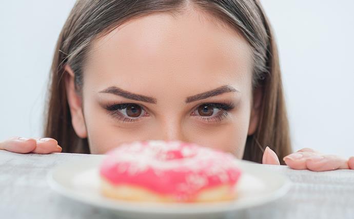 woman staring at a pink donut
