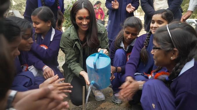 In the video Meghan can be seen planting flowers and painting signs with schoolchildren. *(Image: World Vision)*