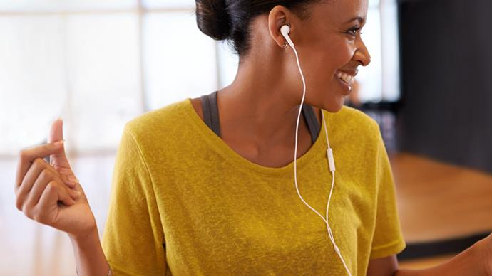 happy woman dancing listening to music on earphones