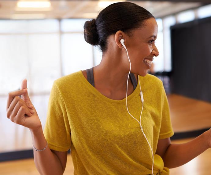 happy woman dancing listening to music on earphones