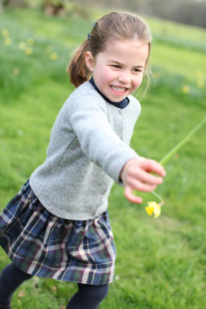 The young royal looks like she was having a fun time as she picks a daffodil for her mum. (*Image: Duchess of Cambridge via PA)*