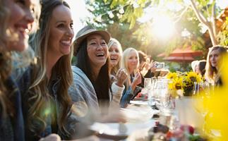 women laughing at a dinner party