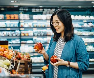 asian woman with glasses choosing apples at the supermarket