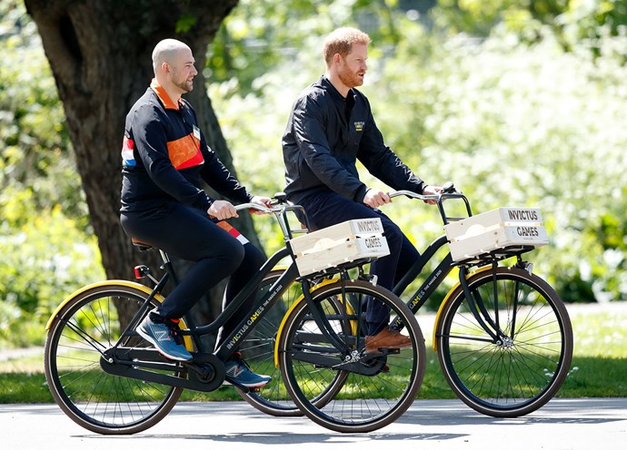 Prince Harry rides around the park where the Invictus Games will be held next year, with former soldier Dennis van der Stroon. *(Image: Getty)*