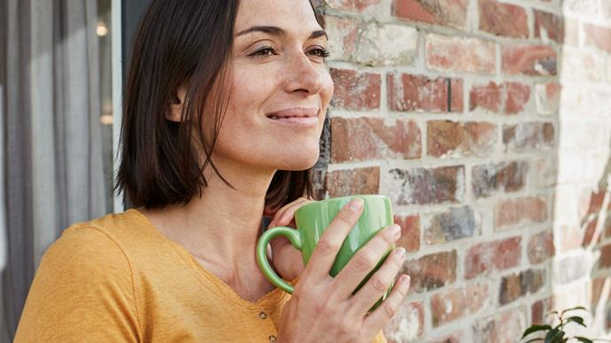 brunette woman smiling drinking coffee