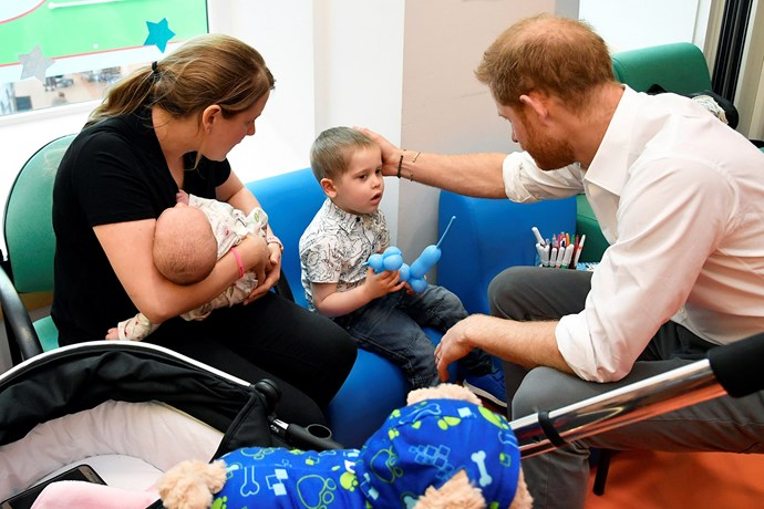 Prince Harry meets Amy Scullard and her two children at Oxford Children's Hospital. *(Image: Getty)*