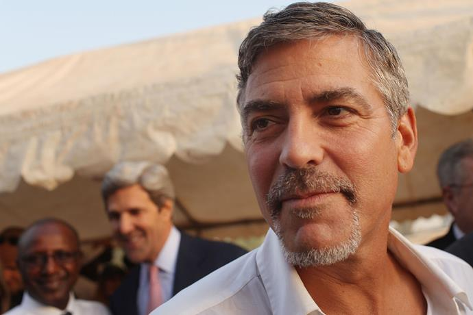 Clooney, with Senator John Kerry in the background, attends voting for the independence referendum in Sudan in 2011. *Photo: Getty*
