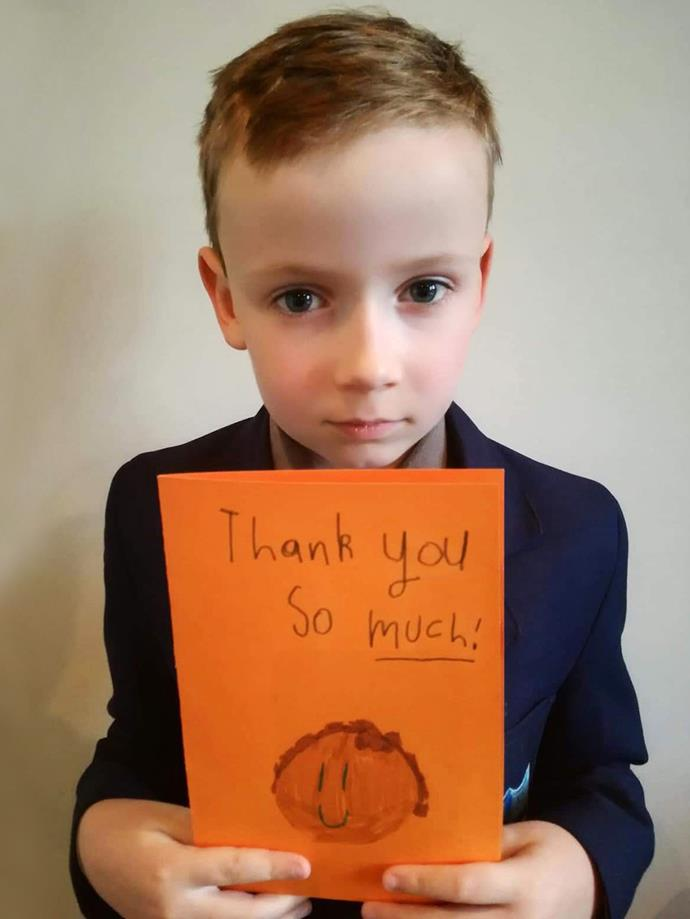 Eight-year-old Finn with the card he made to thank his mother for the work she did after the attacks.