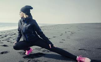 Woman stretching on beach winter