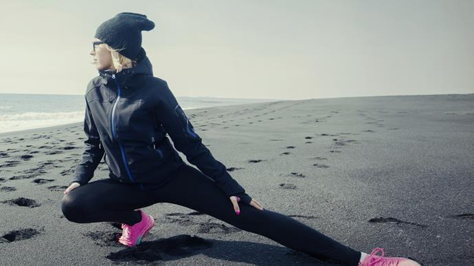 Woman stretching on beach winter