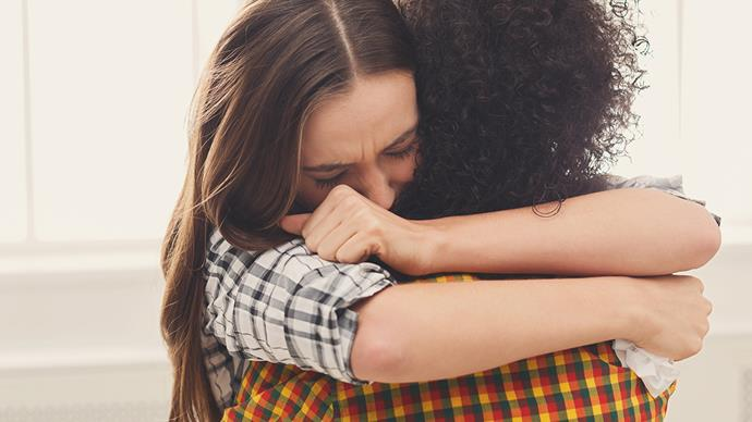 woman hugging friend sad