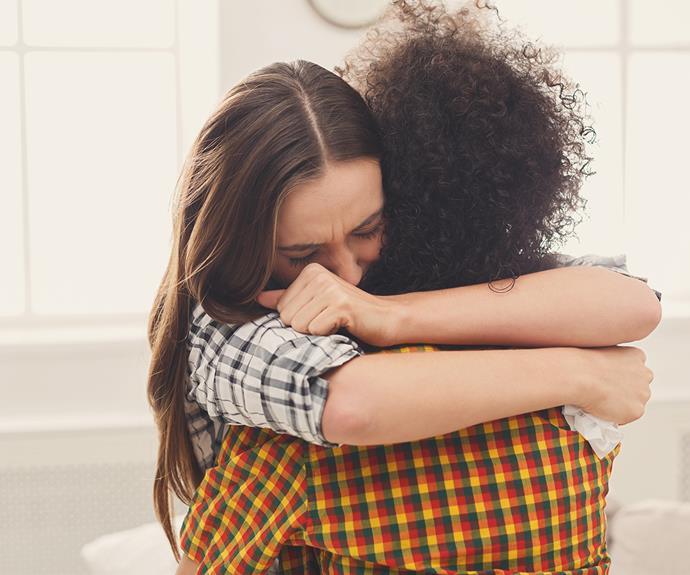 woman hugging friend sad