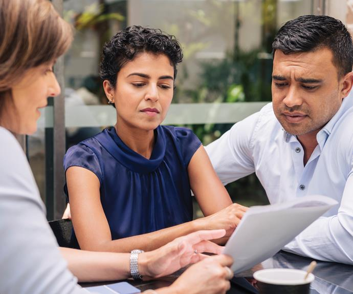 Woman explaining documents to a concerned couple