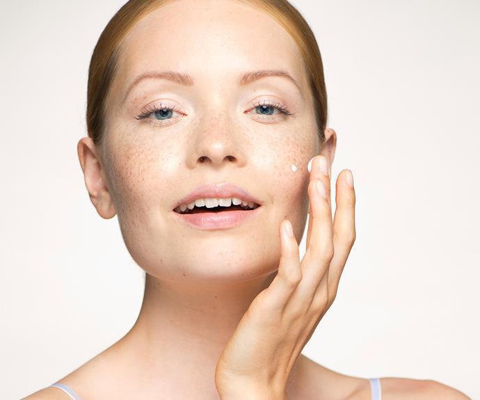 Blonde woman rubbing moisturiser into cheeks