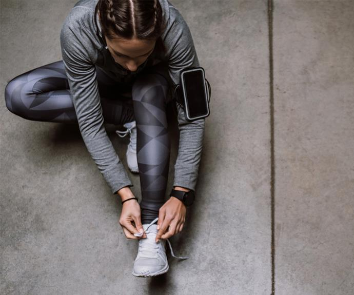 Runner stretching while tying shoe laces